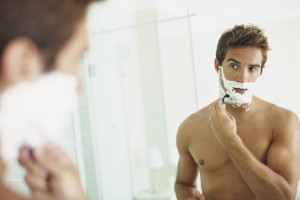 Smart young guy shaving while looking at himself in the mirror